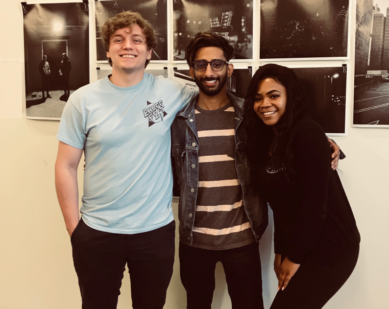 Center for Sustainable Journalism's student experiential learning graduates in front of a Bokeh_Focus photo gallery display. From left to right: Gabe Valeanu, Ali Sardar, Zori Perkins.